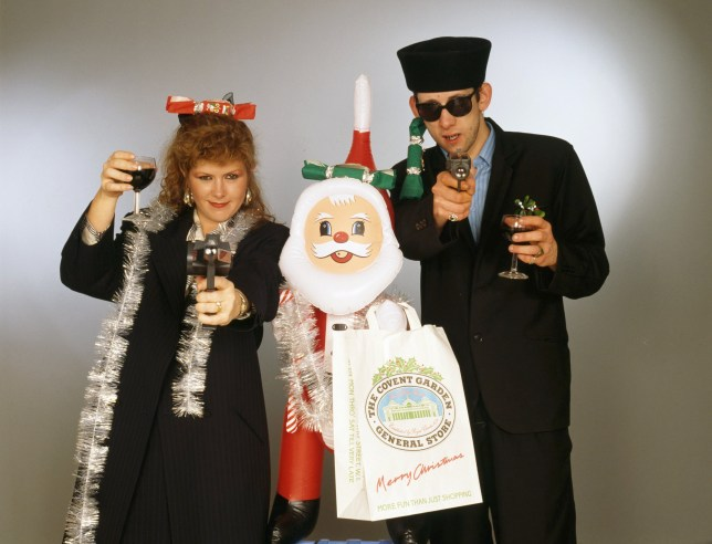 Singers Kirsty MacColl (1959 - 2000) and Shane MacGowan with with toy guns and an inflatable Santa in a festive scenario