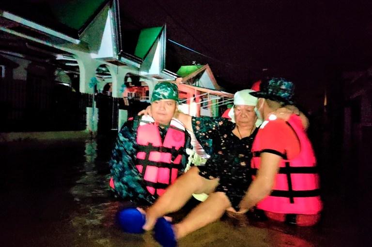 Sur cette photo fournie par les garde-côtes philippins, des sauveteurs portent une femme à la suite de la soudaine montée des eaux de crue alors que le typhon Goni frappe la province de Batangas, au sud de Manille, aux Philippines, le dimanche 1er novembre 2020. Le super typhon a soufflé dans l'est des Philippines avec dimanche de force désastreuse.  (Garde côtière philippine via AP)