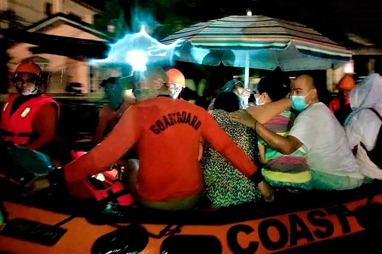 Sur cette photo fournie par les garde-côtes philippins, des membres des garde-côtes philippins utilisent des bateaux en caoutchouc pour secourir les résidents piégés à la suite de la soudaine montée des eaux de crue alors que le typhon Goni frappe la province de Batangas, au sud de Manille, aux Philippines, le dimanche 1er novembre 2020. Le super typhon a soufflé dans l'est des Philippines avec une force désastreuse dimanche.  (Garde côtière philippine via AP)