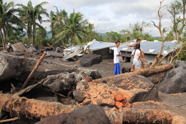 Les résidents se tiennent près de rochers, emportés par les pentes du volcan Mayon à proximité, alors que les maisons sont inondées de boue et de limon dans la ville de Guinobatan dans la province d'Albay le 2 novembre 2020, après que le super typhon Goni a touché terre aux Philippines le 1er novembre. ( Photo par CHARISM SAYAT / AFP) (Photo par CHARISM SAYAT / AFP via Getty Images)