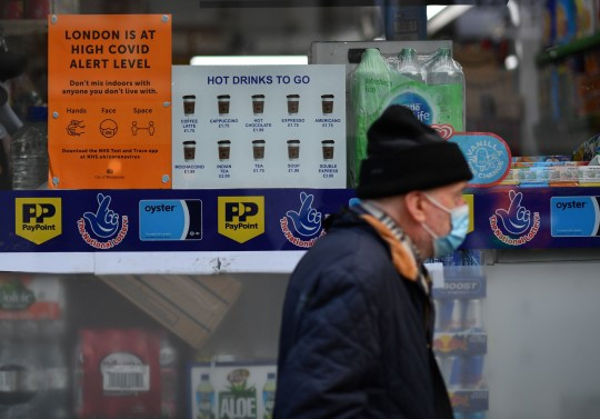 A pedestrian wears a face mask as he walk past a sign in a shop explaining coronavirus restrictions in Chinatown in central London on November 2, 2020. - A second national lockdown is set to come into force from November 5 and end on December 2. (Photo by Ben STANSALL / AFP) (Photo by BEN STANSALL/AFP via Getty Images)