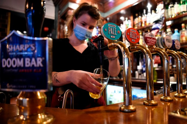 A pub worker wearing a face mask pours a pint
