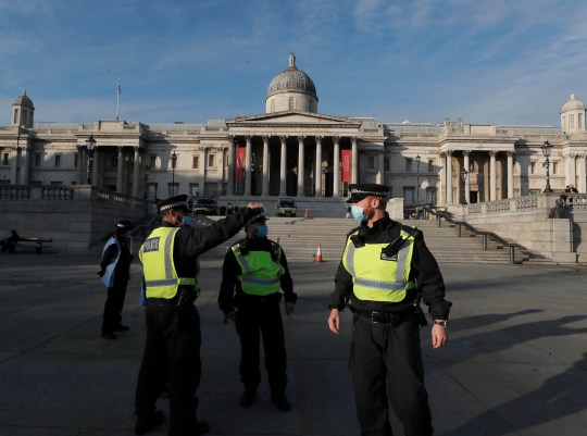 Police stand in front of the National Gallery in Trafalgar Square ahead of an anti-lockdown protest in central London, Thursday, Nov. 5, 2020. Britain joined large swathes of Europe in a coronavirus lockdown designed to save its health care system from being overwhelmed. Pubs, along with restaurants, hairdressers and shops selling non-essential items closed on Thursday until at least Dec. 2. (AP Photo/Frank Augstein)