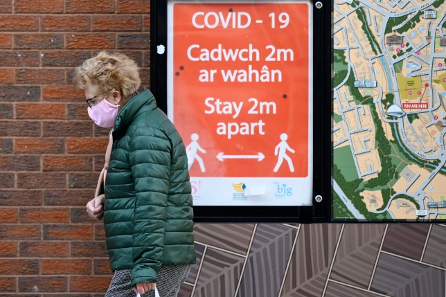 A woman wearing a face covering walks past a social distancing sign