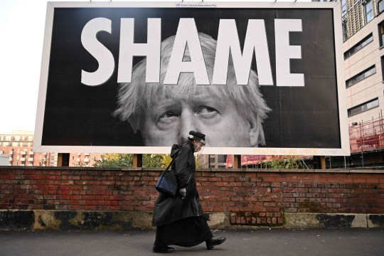 TOPSHOT - A woman wearing a protective face shield passes a billboard showing Britain's Prime Minister Boris Johnson in Manchester, north-west England on November 6, 2020, as the second lockdown comes into force in England. - A united effort to tackle spiking coronavirus infection rates has been called for as 56 million people in England went into a second lockdown but with the public weary of restrictions and fearing for their livelihoods. (Photo by Oli SCARFF / AFP) (Photo by OLI SCARFF/AFP via Getty Images)