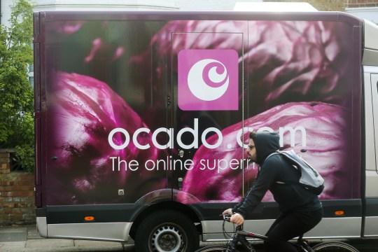 cyclist goes past Ocado food delivery van