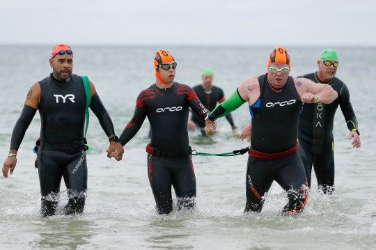 PANAMA CITY BEACH, FLORIDA - NOVEMBER 07: Chris Nikic (2L) exits the swim portion with his guide, Daniel Grieb (R), during IRONMAN Florida on November 07, 2020 in Panama City Beach, Florida. Chris Nikic is attempting to become the first Ironman finisher with Down syndrome. (Photo by Michael Reaves/Getty Images for IRONMAN)