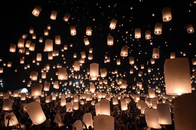 TOPSHOT - People release thousands of paper lanterns to mark the annual Yi Peng festival in the popular tourist city of Chiang Mai in the north of Thailand on November 14, 2016. Tourist arrivals to Thailand have not been hit by a strict mourning period for late King Bhumibol Adulyadej, authorities said, as curbs on entertainment and celebration imposed since his death one month ago were eased. / AFP / LILLIAN SUWANRUMPHA (Photo credit should read LILLIAN SUWANRUMPHA/AFP via Getty Images)