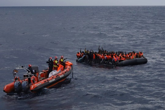 Refugees and migrants wait to be rescued by members of the Spanish NGO Proactiva Open Arms, after leaving Libya trying to reach European soil aboard an overcrowded rubber boat in the Mediterranean sea, Wednesday, Nov. 11, 2020. The Open Arms rescue ship had been searching for the boat in distress for hours before finally finding it Wednesday morning in international waters north of Libya. The NGO had just finished distributing life vests and masks to the passengers to begin transferring them to safety when the flimsy boat split in half throwing them into cold waters. (AP Photo/Sergi Camara)