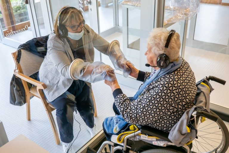 Resident holds hands with a relative through a plastic sheet installed in a special 'hug room' organised to keep both parties safe from novel coronavirus infection, at a care home in Castelfranco Veneto, Italy, in this handout photo released on November 11, 2020. Centro residenziale per anziani Domenico Sartor/Handout via REUTERS ATTENTION EDITORS THIS IMAGE HAS BEEN SUPPLIED BY A THIRD PARTY.