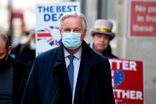 EU chief negotiator Michel Barnier wearing a face mask because of the novel coronavirus pandemic, is followed down a street by Anti-Brexit activist Steve Bray (R) as talks continue between the EU and the UK in London on November 13, 2020.