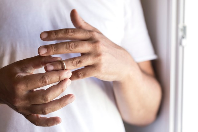 Hands of male wearing white t-shirt who is about to taking off his wedding ring.