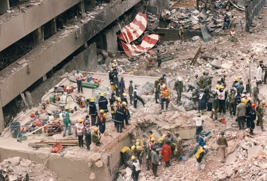 People can be seen trying to find bodies in rubble after a bomb blast