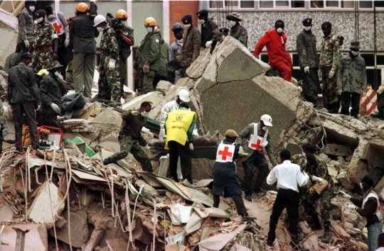 A body is carried out from the wreckage of a bomb blast in Nairobi US embassy blast in Nairobi on