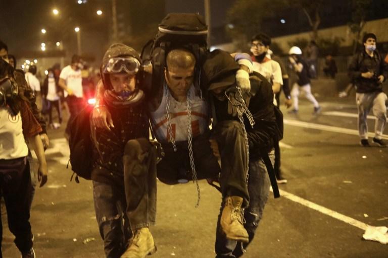Des gens portent un manifestant blessé lors d'une manifestation contre le nouveau gouvernement du président Manuel Merino, sur la place San Martin de Lima, à Lima, Pérou, le 14 novembre 2020.