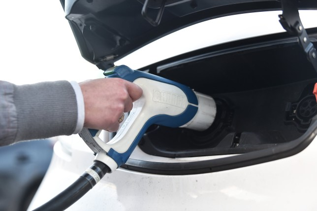 A woman charging an electric car