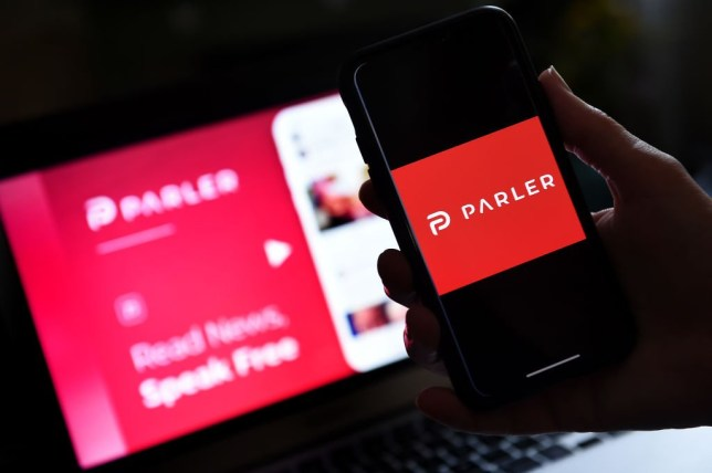 This illustration picture shows social media application logo from Parler displayed on a smartphone with its website in the background