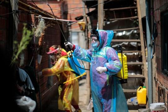 Des agents de santé portant un spray désinfectant EPI sur une maison en Bolivie