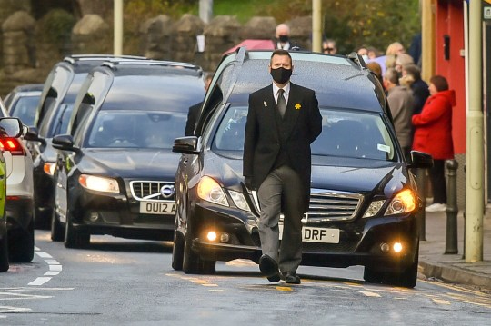 Three hearses process through the main road in Pentre during the funeral of Gladys, Dean and Darren Lewis at St Peter's Church in Pentre, South Wales. Mrs Lewis and her two sons all died of Covid-19 within five days of each other. PA Photo. Picture date: Thursday November 19, 2020. See PA story HEALTH Coronavirus. Photo credit should read: Ben Birchall/PA Wire