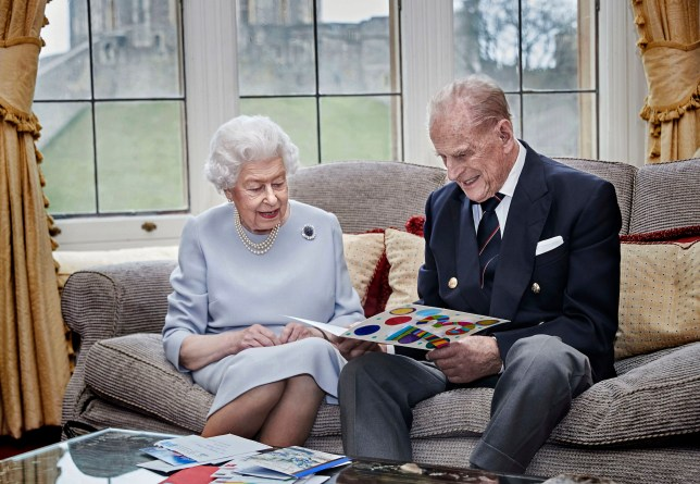Queen Elizabeth II and the Duke of Edinburgh in the Oak Room at Windsor Castle, looking at their homemade wedding anniversary card
