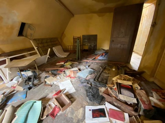 An upstairs bedroom littered with magazines, furniture and broken personal items in an abandoned mansion