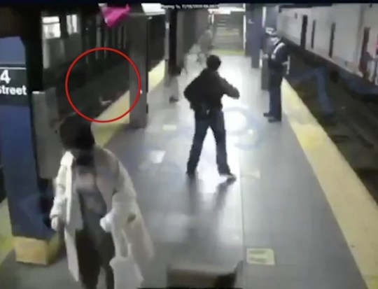 Moment woman is pushed onto tracks in unprovoked attack