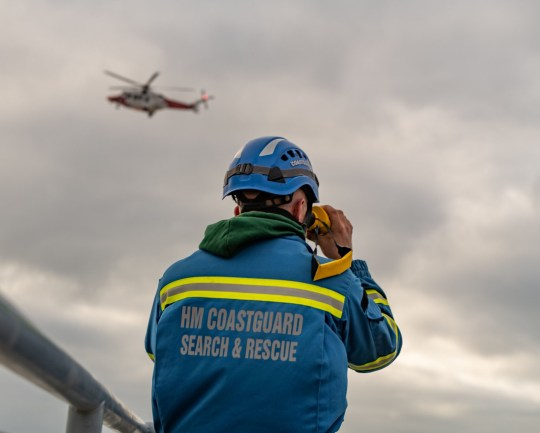 A coastguard scans the rough seas while a search and rescue helicopter searches from the air after a fishing boat sank three miles off the coast at Seaford.
