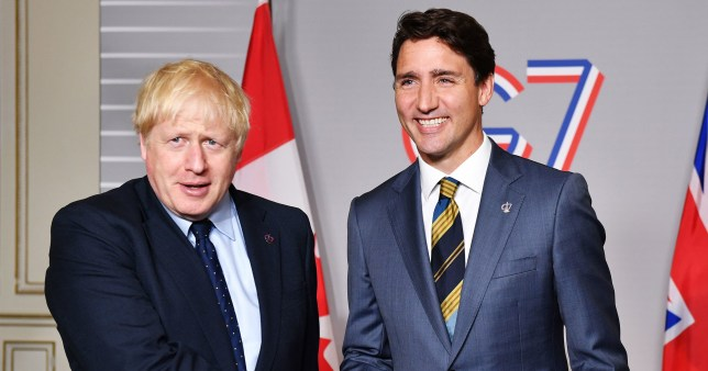 Boris Johnson shakes the hand of a smiling Justin Trudeau