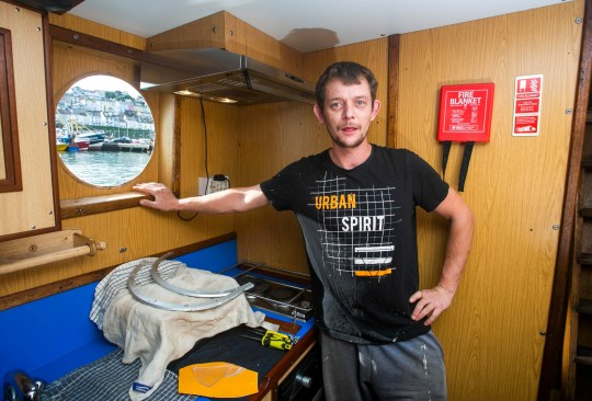 * FILE PHOTO from 2018 of Fisherman Robert Morley next to a smashed window onboard of Golden Promise at the Brixham Harbour in Devon, which was smashed by a rock thrown by french fishermen. See SWNS story SWNNscallop ??? A British boat in the centre of the 'scallop wars' with the French has sunk and coastguards are searching for the missing crew.