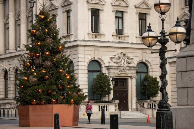 LONDON, ENGLAND - NOVEMBER 23: A member of the public stands beneath a Christmas Tree on lower Regent Street on November 23, 2020 in London, England. UK Prime Minister, Boris Johnson, will announce plans for new coronavirus restrictions to the House of Commons once the current lockdown comes to an end on December 2nd. (Photo by Dan Kitwood/Getty Images)