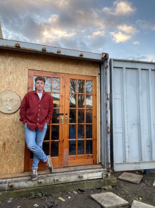 Jay Adler standing outside his shipping container home