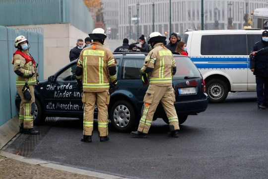 Firefighters work near a car which crashed into the gate of the main entrance of the chancellery in Berlin, the office of German Chancellor Angela Merkel in Berlin, Germany, November 25, 2020. REUTERS/Fabrizio Bensch