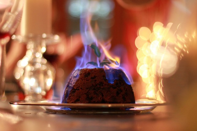 Burning Christmas pudding with a tall, single blue flame. Background of glasses, lights, and table, is blurred and out of focus. Landscape orientation.