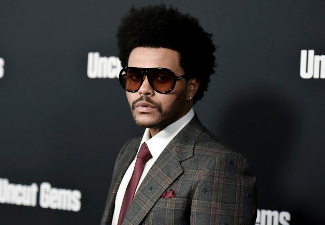 The Weeknd poses on a red carpet