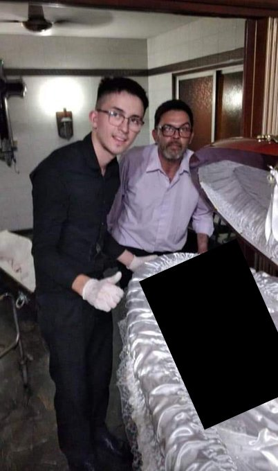 Another funeral parlour employee posed with his thumb up next to Diego Maradona's open coffin