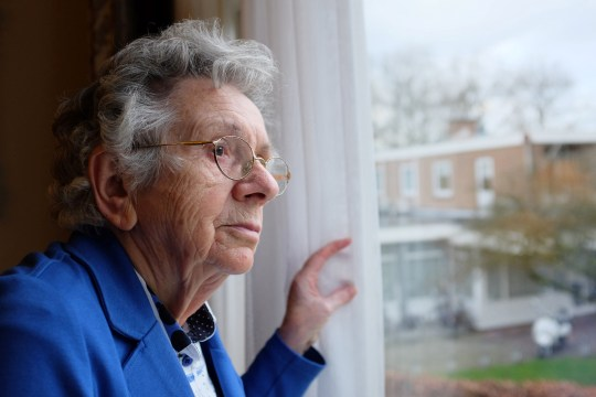 Picture of an old woman looking out of a window