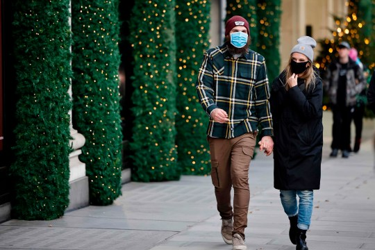 CORRECTION - Pedestrians wearing a masks because of the novel coronavirus pandemic walk past a store front covered in Christmas decorations in central London on November 27, 2020, as life under a second lockdown continues in England. - The current lockdown in England has shuttered restaurants, gyms and non-essential shops and services until December 2, with hopes business could resume in time for Christmas. (Photo by Tolga Akmen / AFP) / CORRECTING DATE The erroneous mention[s] appearing in the metadata of this photo by Tolga Akmen has been modified in AFP systems in the following manner: [November 27, 2020,] instead of [November 20, 2020,]. Please immediately remove the erroneous mention[s] from all your online services and delete it (them) from your servers. If you have been authorized by AFP to distribute it (them) to third parties, please ensure that the same actions are carried out by them. Failure to promptly comply with these instructions will entail liability on your part for any continued or post notification usage. Therefore we thank you very much for all your attention and prompt action. We are sorry for the inconvenience this notification may cause and remain at your disposal for any further information you may require. (Photo by TOLGA AKMEN/AFP via Getty Images)