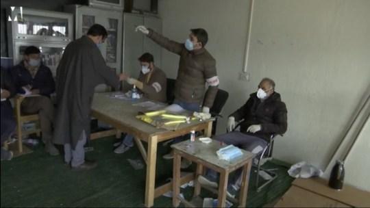 Trois hommes assis à une table en bois portant des masques faciaux alors qu'un homme se penche sur la table pour voter.