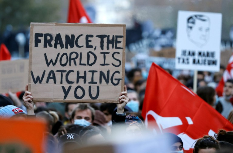 A man holds a sign which says 'the world is watching you'