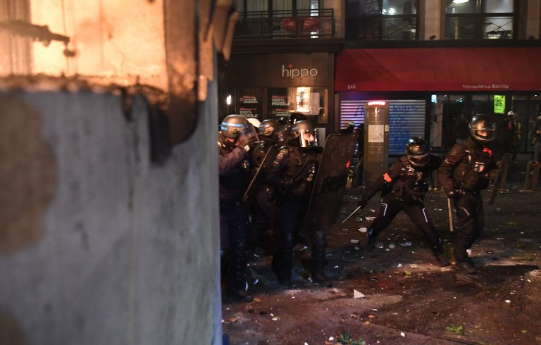 French riot police officers takes cover during a protest against the 'global security' draft law, which Article 24 would criminalise the publication of images of on-duty police officers with the intent of harming their 'physical or psychological integrity', in Paris,