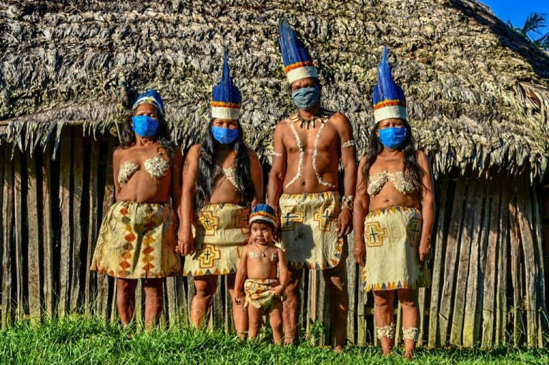 TOPSHOT - Colombian Huitoto indigenous people pose wearing face masks, amid concerns of the COVID-19 coronavirus, in Leticia, department of Amazonas, Colombia on May 20, 2020. (Photo by Tatiana de Nev?? / AFP) (Photo by TATIANA DE NEVO/AFP via Getty Images)