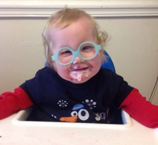 gideon, who has prader-willi syndrome, eating yoghurt and sitting in a high chair