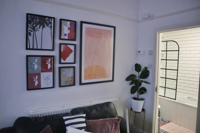 paintings and prints above sofa and indoor plant
