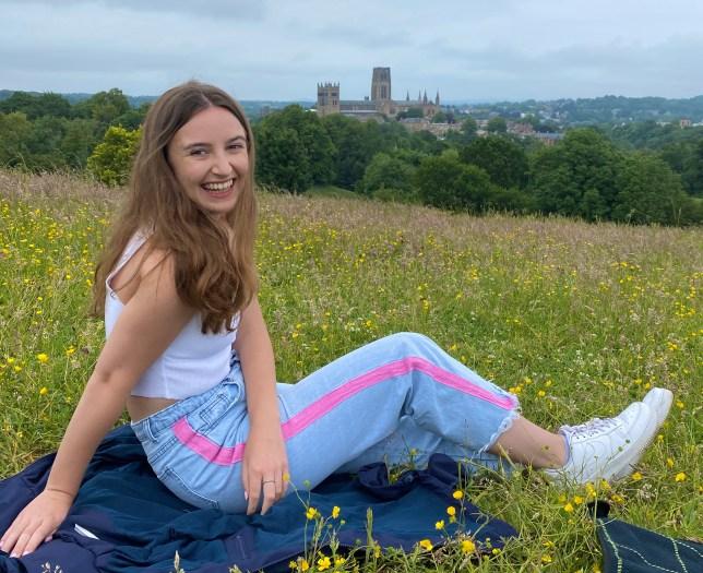 Darcey Sergison sitting on a grassy hill