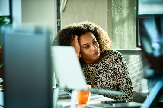 Portrait of mixed race woman looking bored at desk