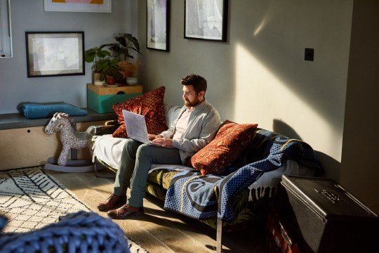 Mature man with beard working from home on laptop