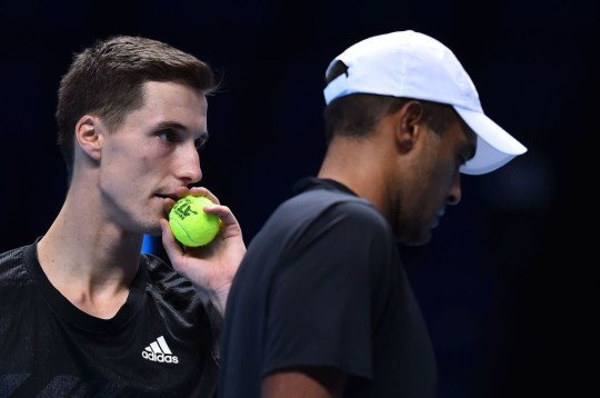 Britain's Joe Salisbury (L) whispers to USA's Rajeev Ram against Poland's Lukas Kubot and Brazil's Marcelo Melo in their men's doubles round-robin match on day one of the ATP World Tour Finals tennis tournament at the O2 Arena in London on November 15, 2020.