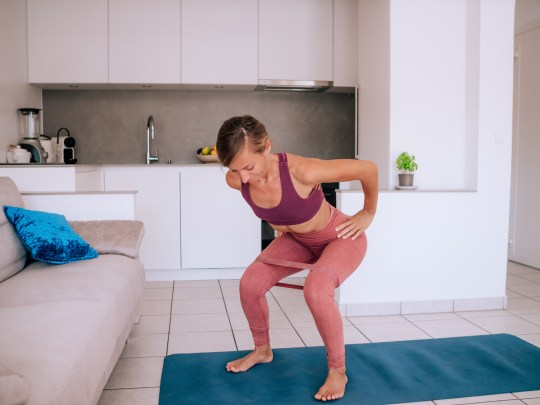 Young woman exercising at home doing so indoor workouts using a resistance band