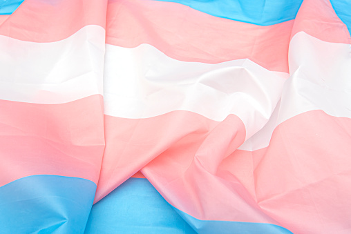 Transgender fabric flag with white, pink, blue strips. Close-up transgender pride flag as background or texture