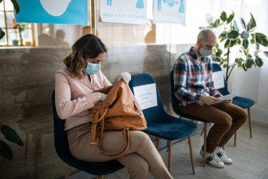 Clients with protective face masks keeping social distancing in bank waiting room